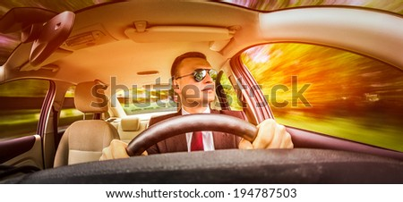 Man in a suit and sunglasses driving on a road in the car. - stock photo