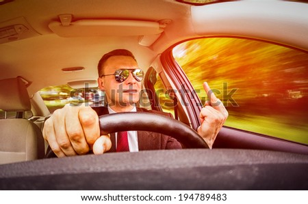 Man in a suit and sunglasses driving on a road in the car. Shows the middle finger to the opponent. - stock photo