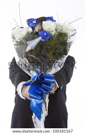 man in a suit giving a bunch of roses blue and white - stock photo