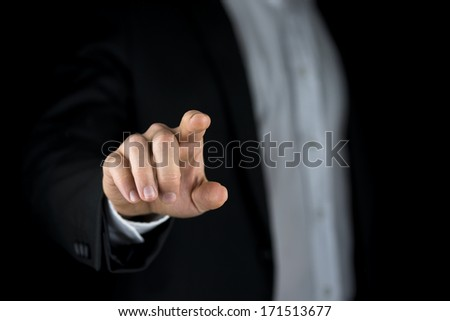 Man in a suit reaching out and touching a blank virtual interface with his finger to activate the connection or making a gesture with his finger and thumb indicating a small quantity or amount - stock photo