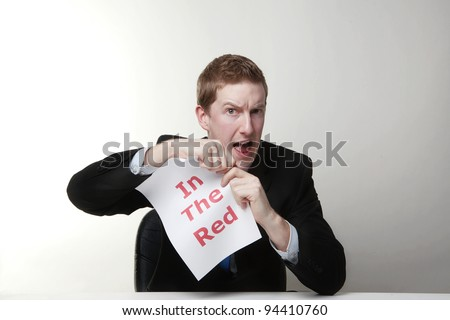 man in a suit sat at a desk ripping a  piece of paper up with the words in the red printed on it and looking happy doing so. - stock photo