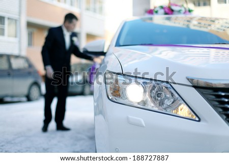 man in a suit sits in a large white car - stock photo