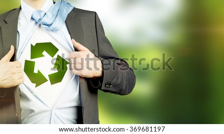 man in a suit with a tie on his shoulder and shirt undone, a green sign of recyclable energy on a white background under it. No face. Concept of eco-friendly consumption. - stock photo