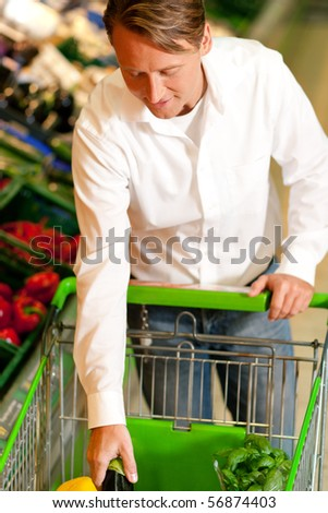 Man in a supermarket at the vegetable shelf shopping for groceries, he is putting some stuff into the shopping cart - stock photo