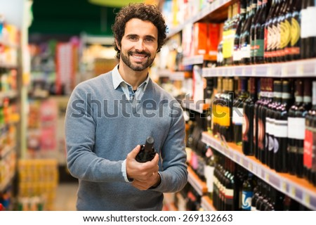 Man in a supermarket choosing a wine bottle - stock photo