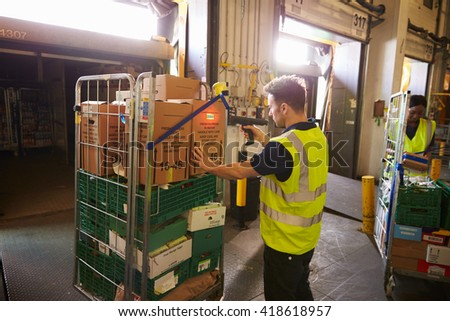 Man in a warehouse holds and scans a box for delivery - stock photo