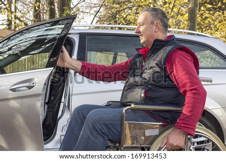 Man in a wheelchair in the fall next to their car - stock photo
