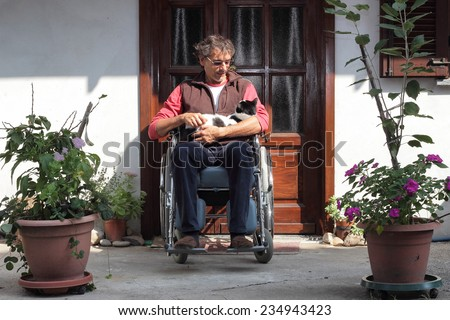 man in a wheelchair with a cat - stock photo