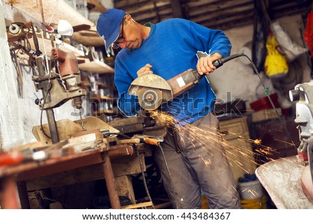 Man in a work shop grinding. - stock photo