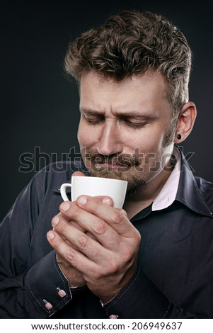 Man in admiration hold a cup of coffee in his hands and enjoying its smell. Close up portrait coffe fan.  - stock photo