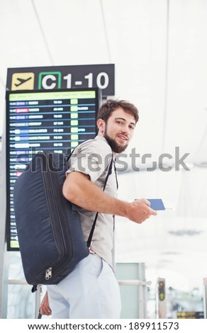 Man in airport holding his passport and hurrying for his flight near the schedule - stock photo