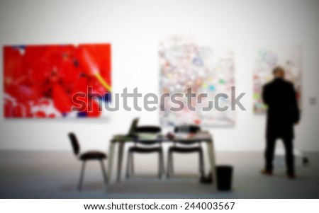 Man in art gallery. Intentionally blurred background, people not recognizable. - stock photo