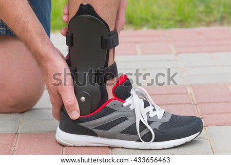 Man in athletic sneakers checking his ankle orthosis or brace on the street - stock photo