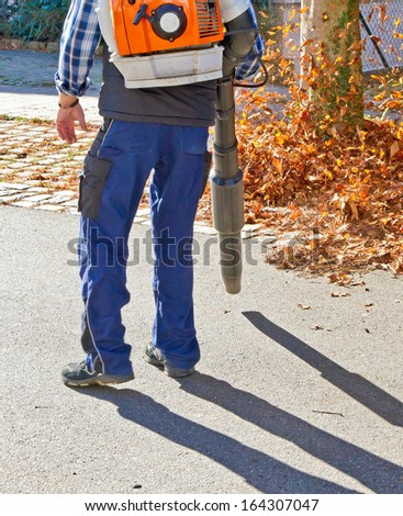 Man in autumn with a leaf blower - stock photo