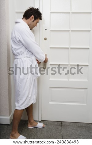 Man in Bathrobe Locked Out of Room - stock photo