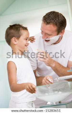 Man in bathroom putting shaving cream on young boy's nose - stock photo