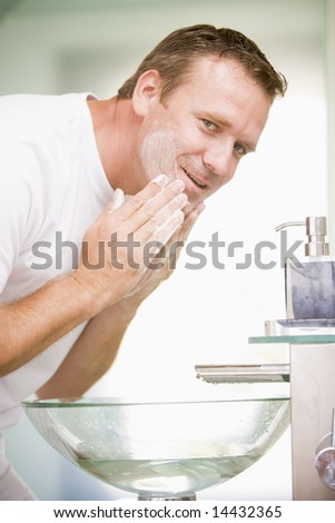 Man in bathroom washing face - stock photo