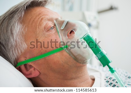 Man in bed with oxygen mask in hospital - stock photo