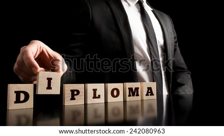 Man in Black Business Suit Arranging Small Wooden Pieces with Diploma Letters on Black Background. - stock photo