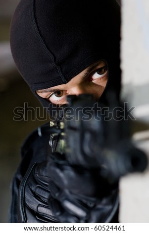 Man in black camouflage targeting with an AK-47 automatic rifle - stock photo