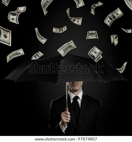 man in black costume with blak umbrella under rain of  currency note,  concept economics  crisis - stock photo