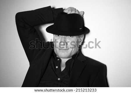 Man in black hat at the age of forty-six years old put his hand on his hat looking at the camera  on the background of a rough wall with texture - stock photo