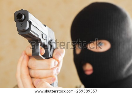 Man in black mask holding gun and ready to use it - stock photo