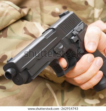 Man in black mask holding gun behind his back - stock photo