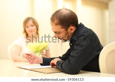 man in black shirt making sign on wedding documents, bride on background - stock photo