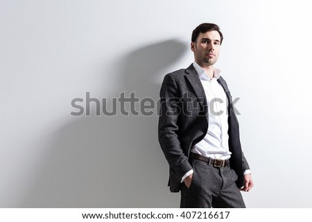 Man in black suit against white wall. Mock up - stock photo