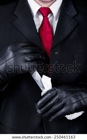 Man in black suit and leather gloves cleaning knife, close up - stock photo