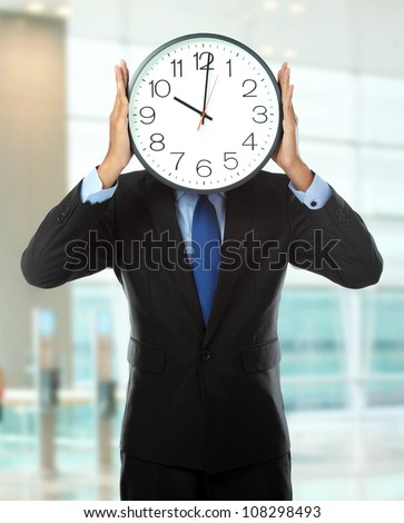 man in black suit holding big clock covering his face in the office - stock photo