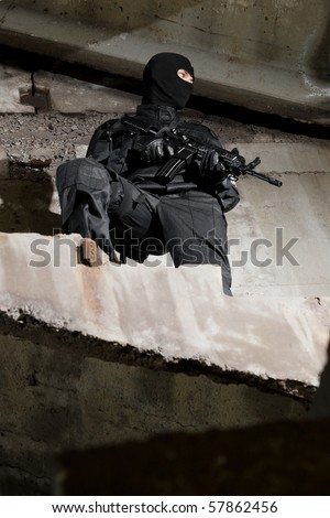 Man in black uniform holding M-4 rifle standing on stairs - stock photo