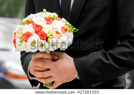 Man in black wedding suit, bridal bouquet with orange roses. Beautiful white wedding bouquet in bridegroom hand - stock photo