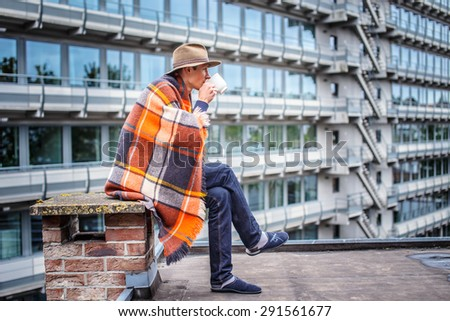 Man in blanket drinking coffe on the roof of multifamily houses. - stock photo