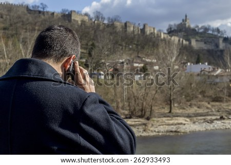 Man in blue coat holding his smartphone  - stock photo
