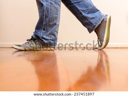 Man in blue jean walking on wooden floor - stock photo