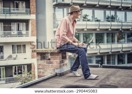 Man in blue jeans and pink shirt sitting on the roof with laptop. - stock photo