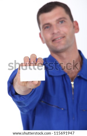 Man in blue overalls holding a business card left blank for your details - stock photo