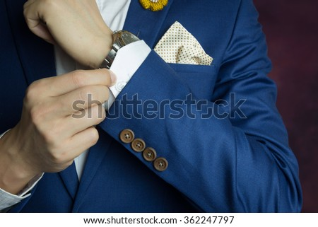 Man in blue suit two bottons, doing button, close up - stock photo
