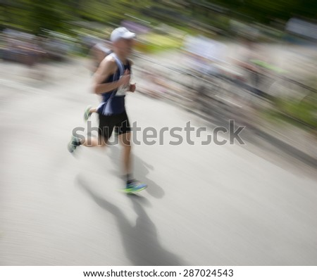 Man in blurred motion in running competition - stock photo