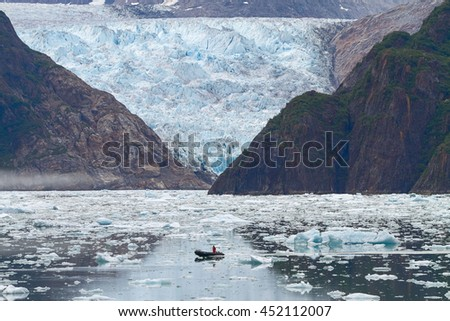 Man in Boat in Front of Sawyer Glacier at Tracy Arms Fjords in Alaska United States. - stock photo