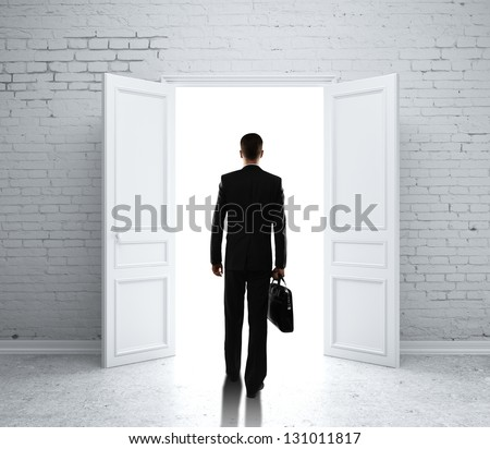 man in brick room with open door - stock photo