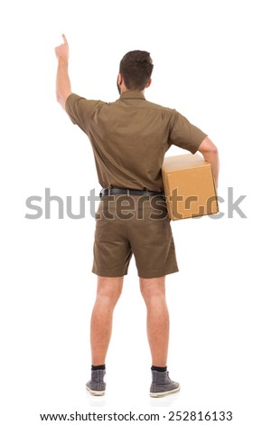 Man in brown uniform holding package under his arm and pointing up. Rear view. Full length studio shot isolated on white. - stock photo