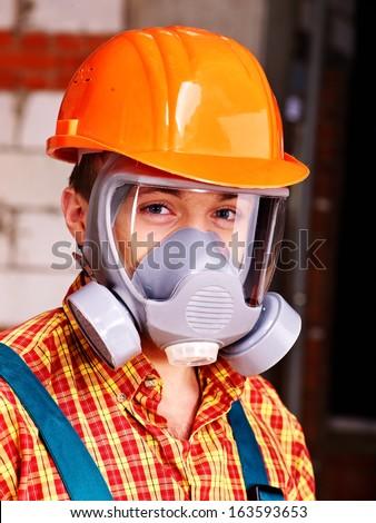 Man in builder  respirator indoor. - stock photo