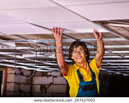 Man in builder uniform installing suspended ceiling - stock photo