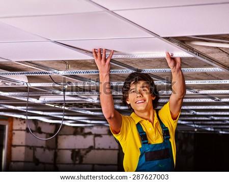Man in builder uniform installing suspended ceiling - stock photo