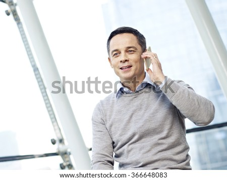 man in business casual wear making a phone call in office. - stock photo