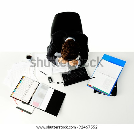 Man in business suit sits stressed out at his desk when he is faced with too much work - stock photo