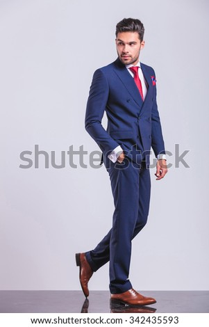 man in business suit walking while looking away with hand in pocket - stock photo